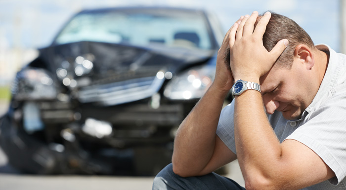 Frustrated man sits in front of a totaled vehicle, in need of a Miami car accident lawyer